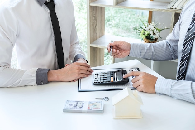Sale purchase contract to buy a house, real estate agent are presenting home loan and giving keys to customer after signing contract to buy house with approved property application form.