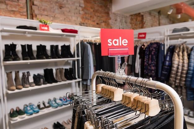 Распродажа красная табличка на стойке для одежды с вешалками