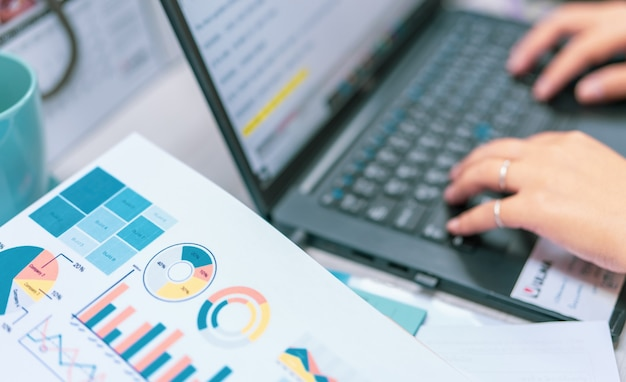 Отчет о продажах и финансовая диаграмма бизнес-графика на размытии руки офисного работника, печатающей на ноутбуке
