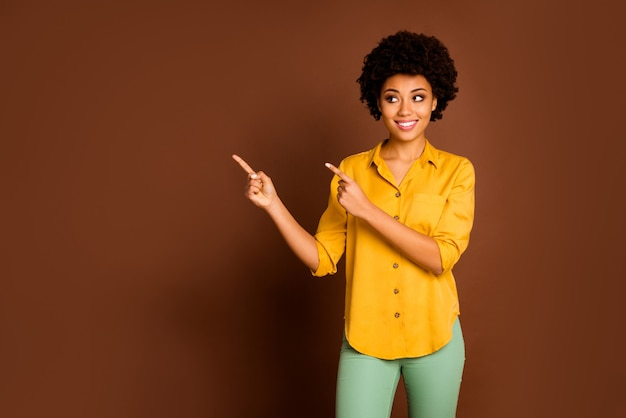 Продажа, продажа, продажа! фотография красивой довольно темной кожи волнистой дамы, указывая пальцами на пустое пространство, низкие цены на покупки, носить желтую рубашку, зеленые брюки, изолированные коричневого цвета