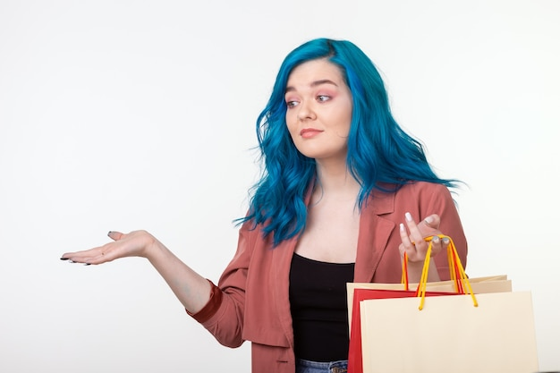 Sale, shopaholic and consumer concept - beautiful girl with blue hair standing with shopping bags