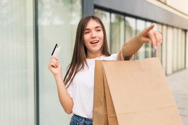 販売、ショッピング、観光、幸せな人々のコンセプト-通りで手に買い物袋とクレジットカードを持つ美しい女性