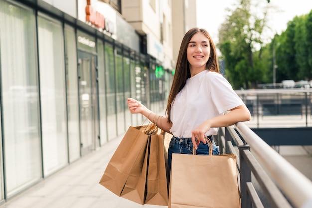 販売、ショッピング、観光、幸せな人々のコンセプト-街の買い物袋を持つ美しい女性