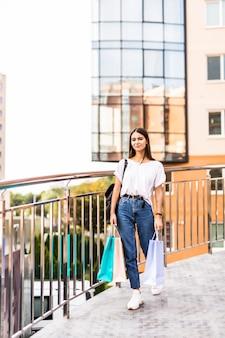 판매, 쇼핑, 관광 및 행복 한 사람들 개념-왕에서 쇼핑 가방을 가진 아름 다운 여자