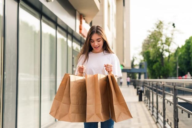 Vendita, shopping, turismo e concetto di persone felici - bella donna con borse della spesa in città