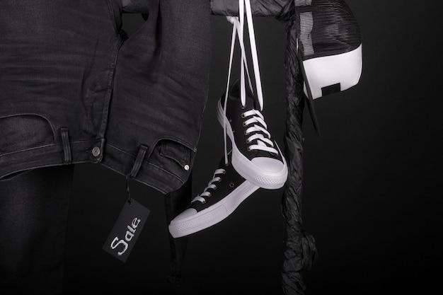 売却の記号。黒と白のスナッカー、キャップとパンツ、ジーンズは黒の背景に洋服ラックに掛かっています。ブラックフライデー。