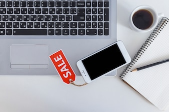 Sale tag on mobile over the open laptop with coffee cup