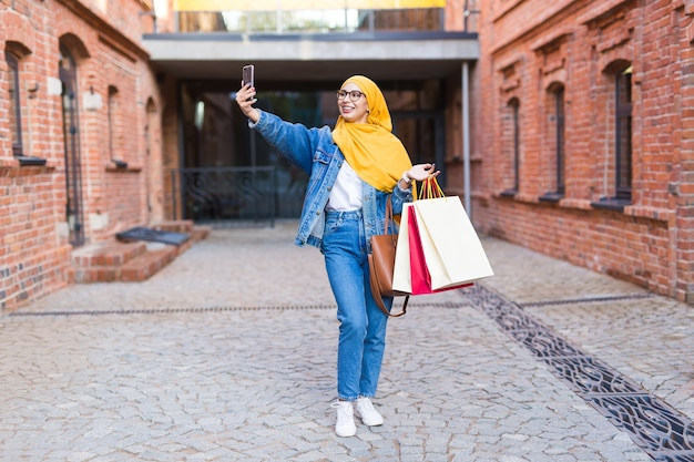 Sale, technologies and buying concept - happy arab muslim woman taking selfie outdoors after