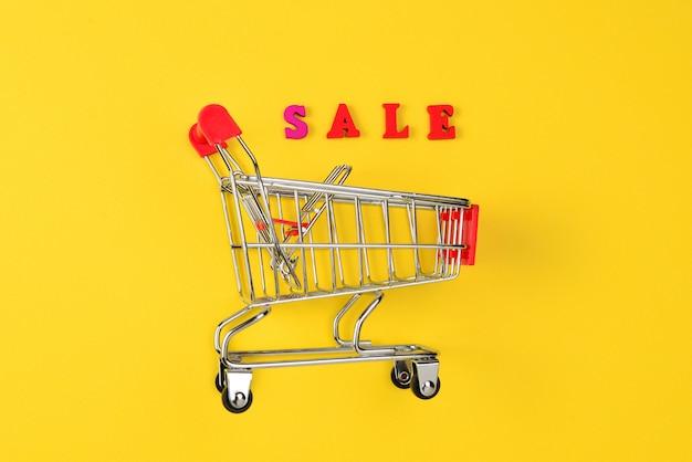 販売テキストと黄色の背景にショッピングカート。