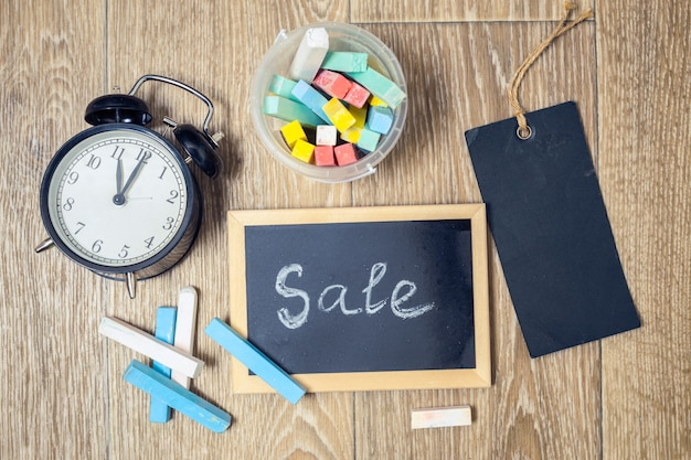 Sale text on chalkboard with chalks and clock