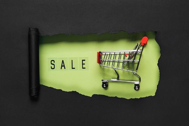 ショッピングカートと緑の穴の背景にテキストを販売します。ショッピング割引プロモーション。