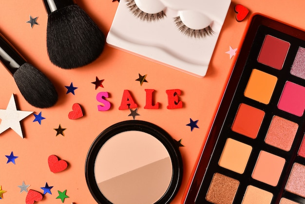 Sale text on an orange background. professional trendy makeup products with cosmetic beauty products,  eye shadows, eye lashes, brushes and tools.