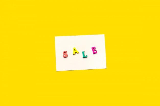 노란색 배경에 고립 된 흰색 카드에 판매 텍스트 쓰기