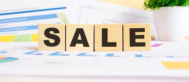 Продажа слово на деревянных кубиках. фон представляет собой бизнес-схему. концепция бизнеса и финансов