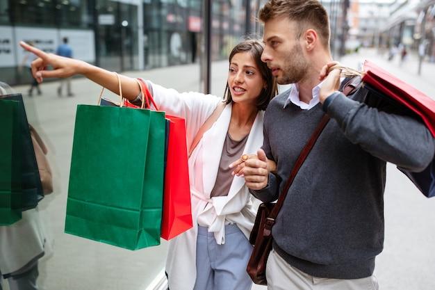 Продажа, путешествия любят потребительство и концепцию людей. счастливая пара с хозяйственными сумками в городе