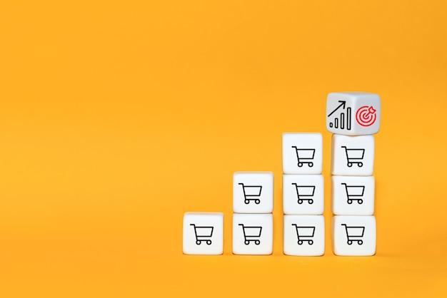 판매량이 증가하면 비즈니스가 성장합니다. 큐브는 아이콘 목표와 쇼핑 카트 기호로 뒤집 힙니다.
