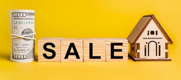 黄色の背景に家のミニチュアモデルとお金で販売。ビジネス、金融、クレジット、税、不動産、住宅、住宅の概念