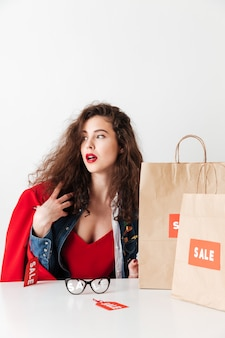판매 여자 종이 쇼핑백 함께 앉아서 멀리보고