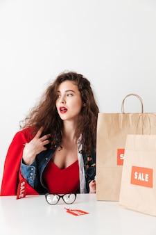 Donna di vendita che si siede con i sacchetti della spesa di carta e distogliere lo sguardo