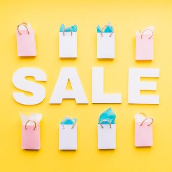 노란색 배경에 채워진 된 쇼핑백의 행 판매 단어