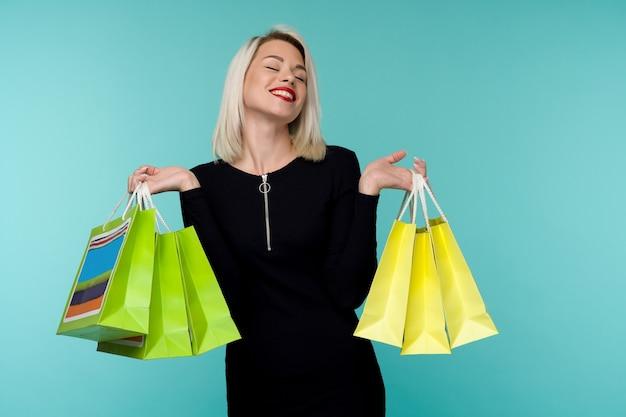 Распродажа. молодая улыбающаяся женщина, держащая хозяйственные сумки в праздник черной пятницы. счастливая девушка на синем фоне