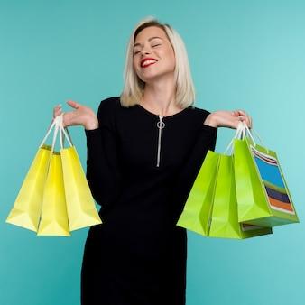 판매. 검은 금요일 휴일에 쇼핑 가방을 들고 젊은 웃는 여자. 파란색 배경에 행복 한 여자