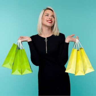판매. 검은 금요일 휴일에 쇼핑 가방을 들고 젊은 웃는 여자.