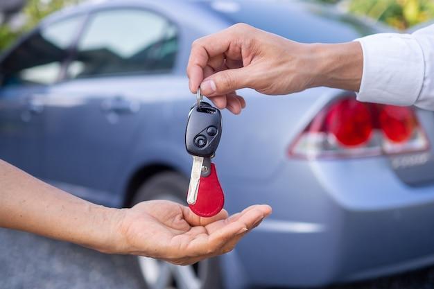 판매 대리점은 자동차를 판매하고 새 소유자에게 키를 제공합니다. 자동차 또는 렌트카 판매
