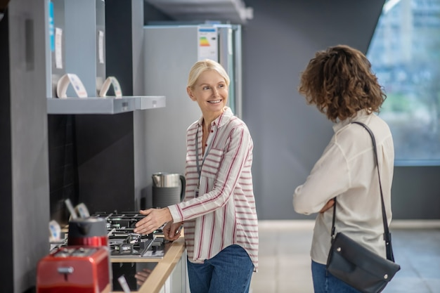 여성 고객에게 상품을 보여주는 스트라이프 셔츠의 판매 도우미