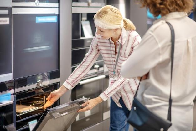 고객에게 새 오븐을 보여주는 스트라이프 셔츠의 영업 도우미 프리미엄 사진