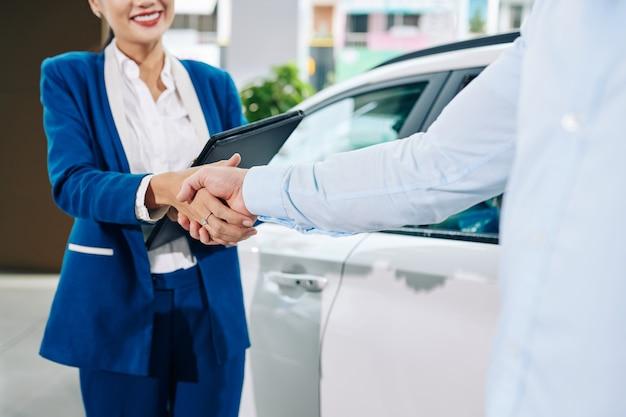 Продавец-консультант пожимает руку клиенту после того, как он покупает автомобиль в автосалоне