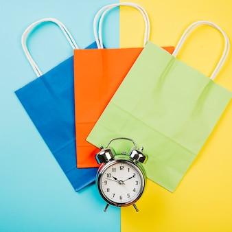 Concetto di vendita con tre borse e sveglia