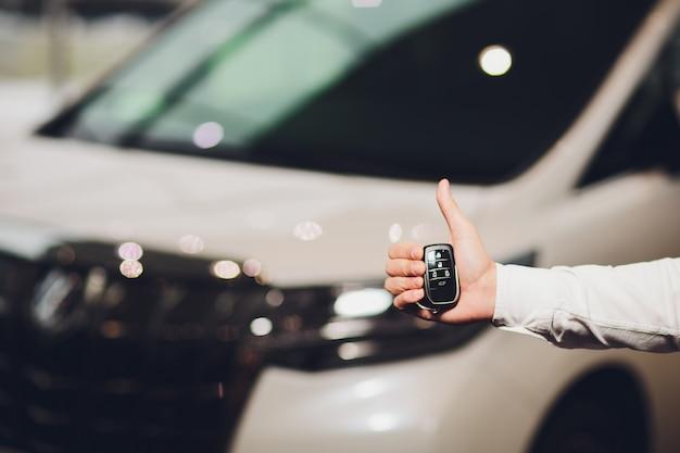 백그라운드에서 자동차와 자동차 키 근접 촬영을주는 영업 임원.