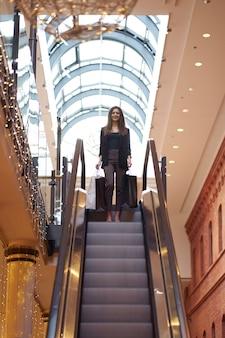店頭での販売。ブラックフライデー。ショップの背景に大きな買い物袋で行く流行の服を着ているスタイリッシュな女性。