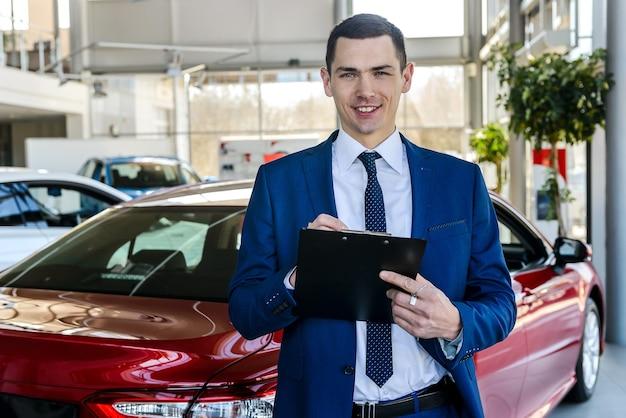 自動車販売店でポーズをとるセールスマン