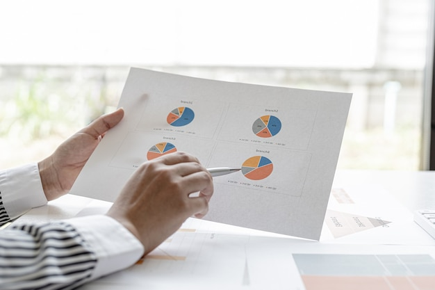 The sales manager points to the sales summary, she is checking the sales of each branch, she checks the information before presenting it in the meeting to the management. sales management concept.
