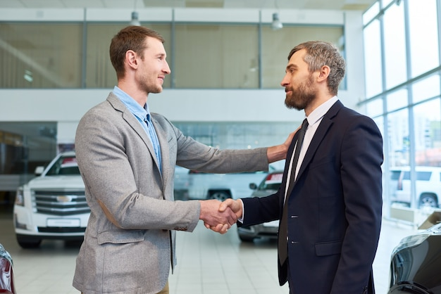 Sales manager shaking hands with client buying car