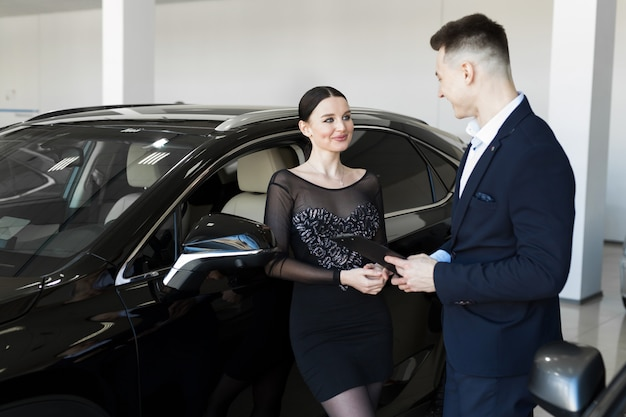 Sales manager showing a woman a new car