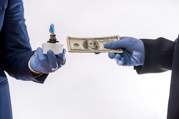 Sales in quarantine conditions coronavirus hands holding car light bulbs and dollar bills isolated. buying car concept