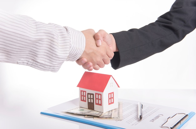 Salesman agent handshake with customer after agreement contract sale home.