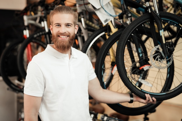A salesman in a bicycle shop poses near a bicycle.