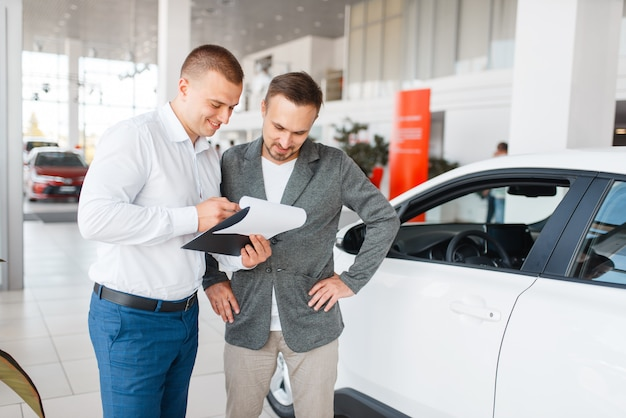 Salesman and buyer make out the purchase of new car in showroom. male customer buying vehicle in dealership, automobile sale
