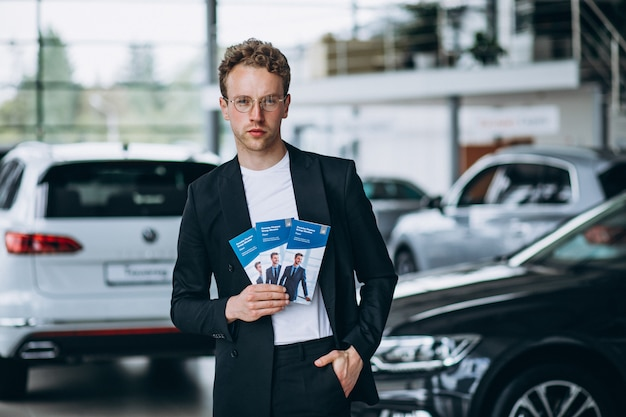 Salesman at a car showroom with business flyers