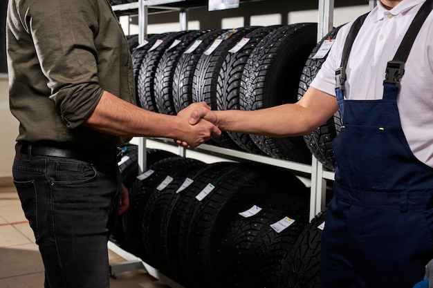 Salesman and customer shaking hands in auto service shop, male made choice, buying car tire for winter