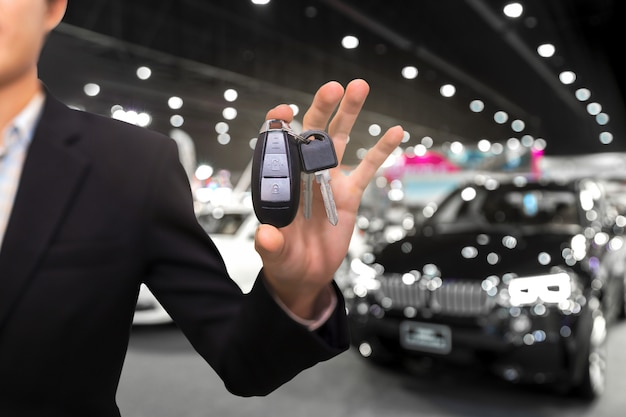 Salesman or dealer offering car keys to new owner in showroom, buy or rent concept.