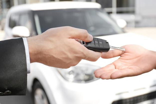 Продавец дает ключ от машины клиенту на открытом воздухе