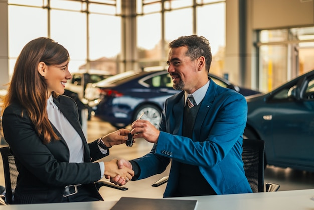 Salesman giving car keys while shaking hand of a woman in a car salon.