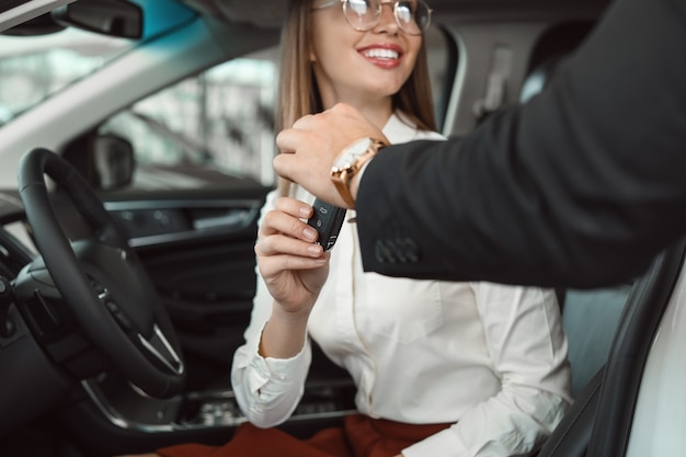 Salesman giving key from new car to young woman