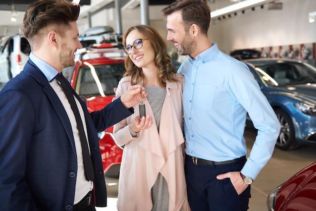 Продавец вручает паре новые ключи от машины