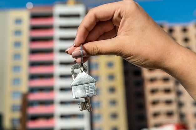 주거 지역 배경에서 키를 나눠주는 세일즈맨. 판매 또는 임대 개념